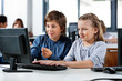 Boy Pointing While Using Desktop Pc With Friend At Desk