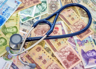 Stethoscopes on top of Chinese currency