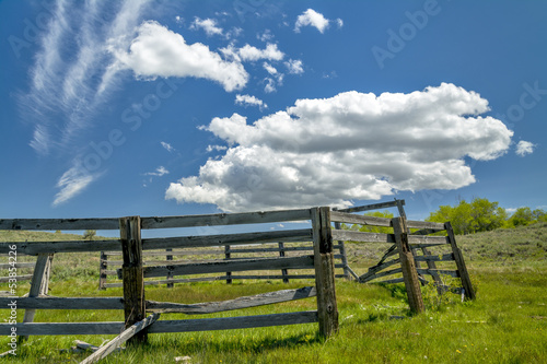 Broken down corral in a field with clouds