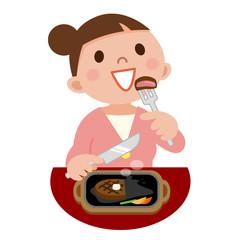 ステーキを食べる女性