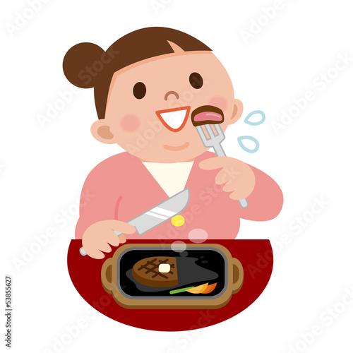 ステーキを食べる太った女性