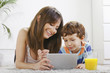 Mother and son having fun with a digital tablet in home