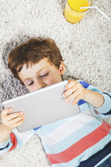Child playing with digital tablet stretched on a carpet