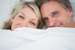 Couple smiling from under the covers