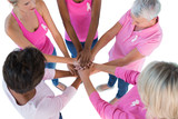Group wearing pink and ribbons for breast cancer with hands toge