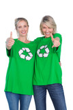 Two blonde women wearing green recycling tshirts giving thumbs u