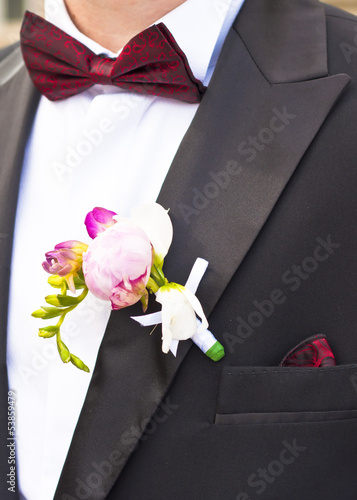Close-up of Poeny pink flower on Groom's Tuxedo