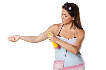 Smiling pretty girl applied a sunscreen spray
