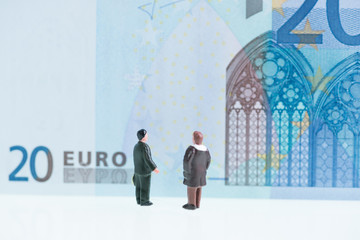 Miniature men looking at twenty Euro banknote background