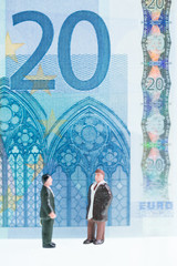 Miniature men chatting with twenty Euro banknote background