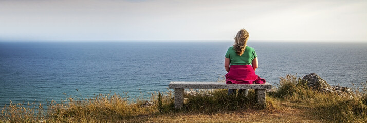A blonde female hiker looking out to sea - panoramic.