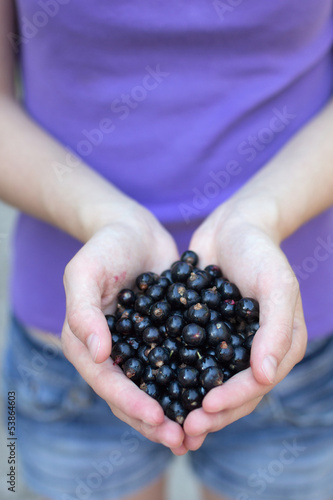 Young woman holding fresh blackcurrants