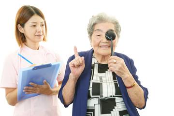 視力検査を受ける笑顔の高齢者と看護師