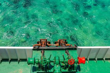 Ships ancor mechanism with clear green waters at background