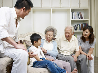 asian family gathering and talking in living room