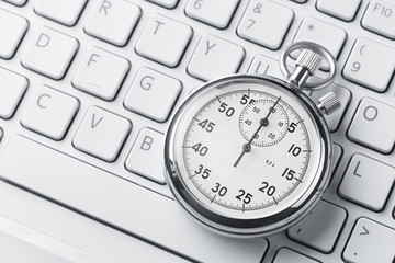 Close up of analog stopwatch on a keyboard