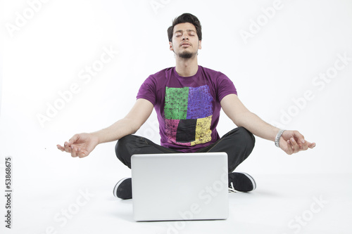 Man meditating infront of a laptop