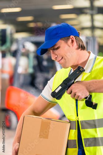 Lagerist von Spedition scannt Paket in einem Lager