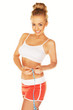 Attractive athletic woman measuring her waist