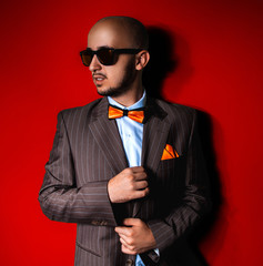 Nice man in sunglasses and suit on red background