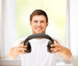 young smiling man offering headphones at home