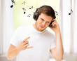 man with headphones listening rock music at home