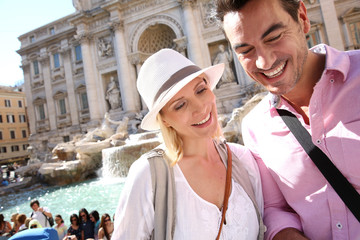 Tourists in Rome standing by the Trevi fountain