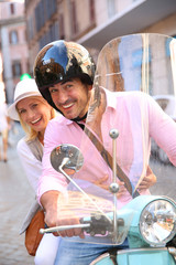 Cheerful couple in Rome riding scooter