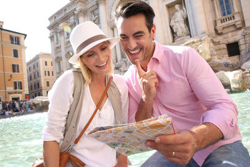 Couple reading city map by the Trevi Fountain of Rome