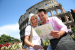 Tourists reading map in front of the Coliseum, Rome