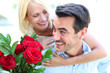 Man giving red roses to woman