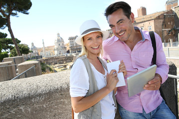 Couple of tourists using tablet to visit Rome Capital