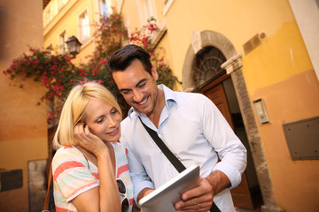 Couple of tourists visiting Rome with help of tablet