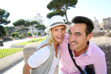 Smiling couple of tourists visiting Rome, Italy