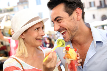 Couple of tourists having fun eating fresh fruits