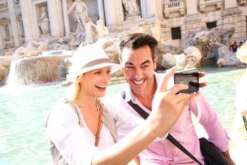 Couple taking picture in front of the Trevi Fountain