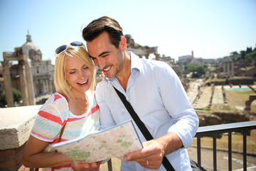 Couple of tourists reading city map by the Roman Forum