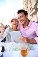 Tourists in Rome using tablet while having drink
