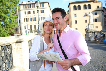 Tourists in Rome reading map on Saint Angel's bridge