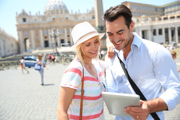 Couple of toursits using digital tablet in Rome