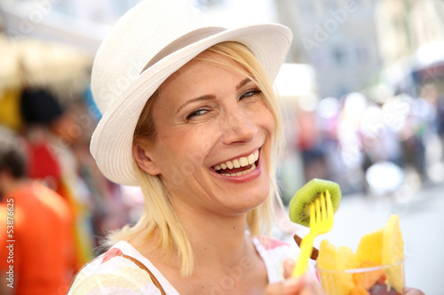 Cheerful blond girl eating fresh fruits in summer
