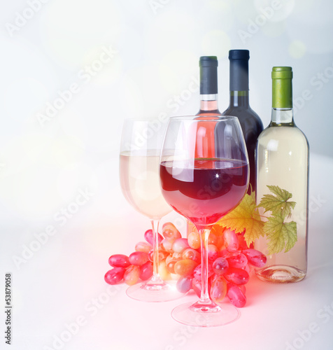 wineglass, bottles of wine and grapes