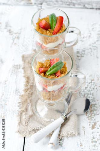 Dessert from sponge cake , strawberries and cream in a glass