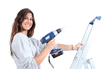 Beautiful woman with a drill on a ladder