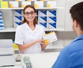 Happy Pharmacist Showing Drug To Client