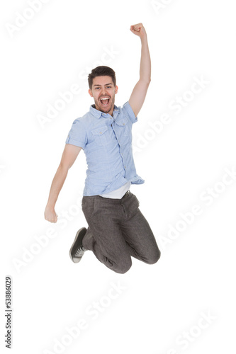 Young Man Jumping With Arms Raised