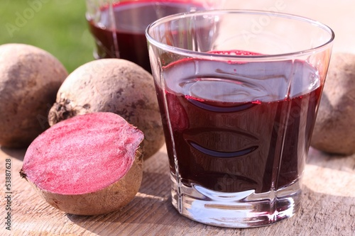 Glass with beetroot juice on garden table
