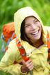 Happy hiker woman hiking in rain with backpack