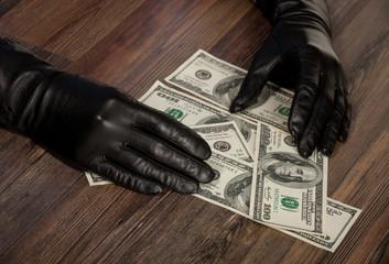 Human hands in black gloves holding dollars