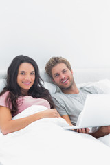 Couple using a laptop in bed